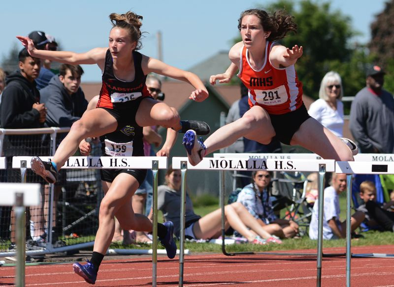 PAMPLIN MEDIA PHOTO: DAVID BALL - Gladstone's Briana Lewis (left) finished second to Molalla's Emma Andrews in the girls' 100-meter hurdles at Saturday's Tri-Valley Conference track and field championships in Molalla.