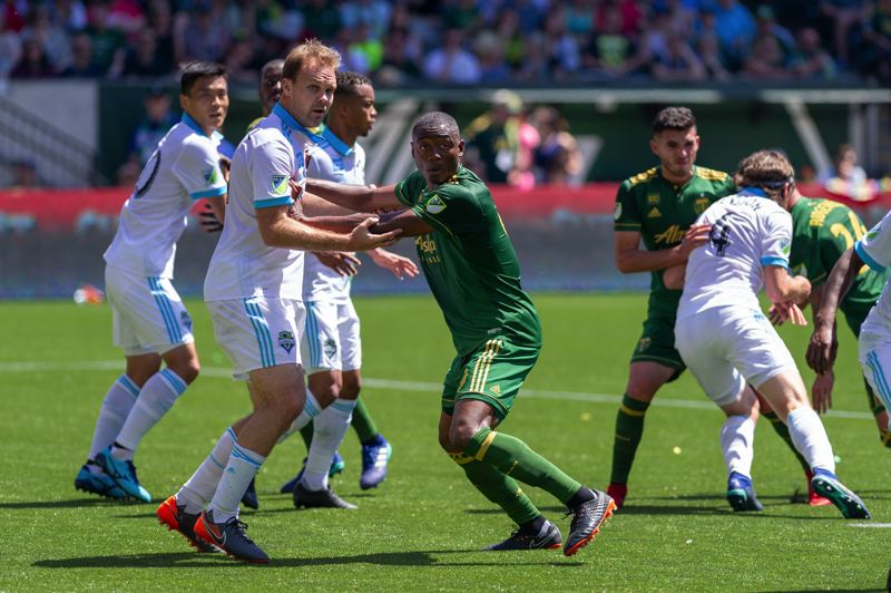 TRIBUNE PHOTO: DIEGO G. DIAZ - Fanendo Adi, Portland Timbers forward, fends off Seattle defender Chad Marshall.
