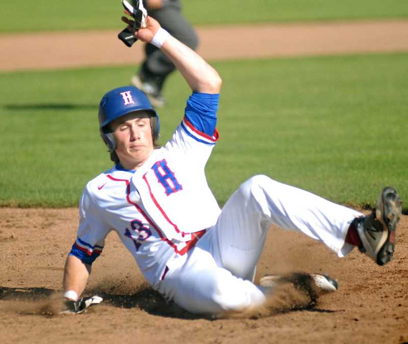 PMG PHOTO: MATT RAWLINGS - Hilhi's Curran Mitzel slides into home during the Spartans' game against Sandy May 11, at Hare Field.
