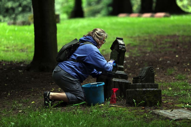 JESSIE DARLAND - Leslie Hole washes a headstone at Lone Fir Cemetery on Saturday.