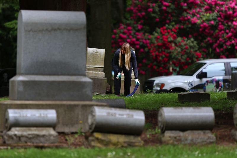 JESSIE DARLAND - A volunteer sets down her mat as she prepares to clean a headstone.