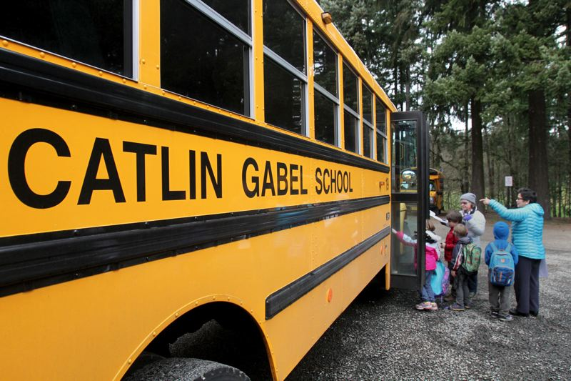 TRIBUNE FILE PHOTO - Students line up at a clean-diesel bus serving Catlin Gabel School on the westside. More than 450 older, dirty-diesel school buses will be replaced statewide, thanks to a legal settlement with Volkswagen.