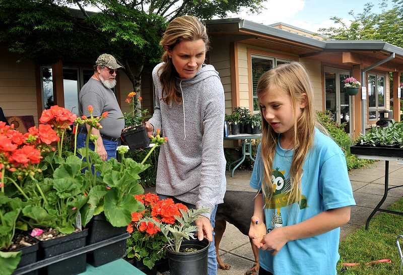 Charity Hudnutt and her daughter Julia, 8, pick out some plants.
