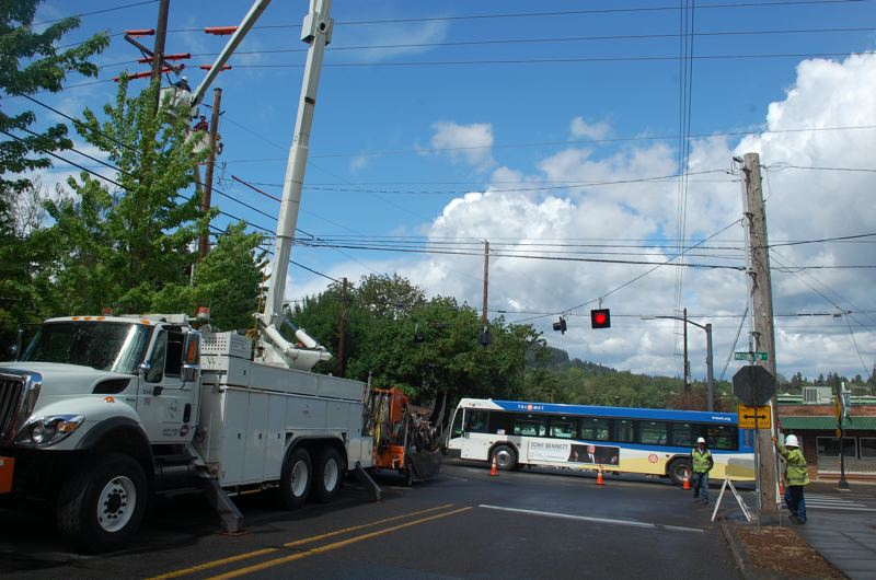 PHOTO BY: RAYMOND RENDLEMAN - PGE construction workers block lanes at Oregon Citys 12th/Washington intersection as they prepare overhead wires for a new traffic signal.