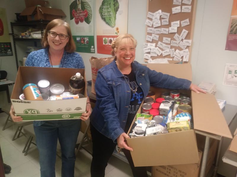 Leslie Robinette, communications coordinator for the Gladstone School District, and Keystone Chiropractic employee Denise Browning show some of the food donated by community members.