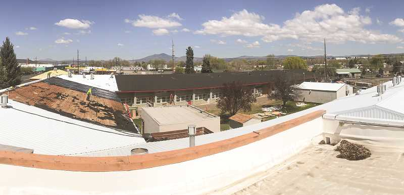 PHOTO SUBMITTED BY ANDY HEWES  -  A photo taken from above the facility as roofing work takes place. Metal roofing was removed and residential composite roofing was installed in its place.