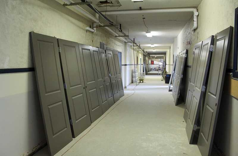 JASON CHANEY/CENTRAL OREGONIAN  - Residential doors await installation in what was once a school hallway.