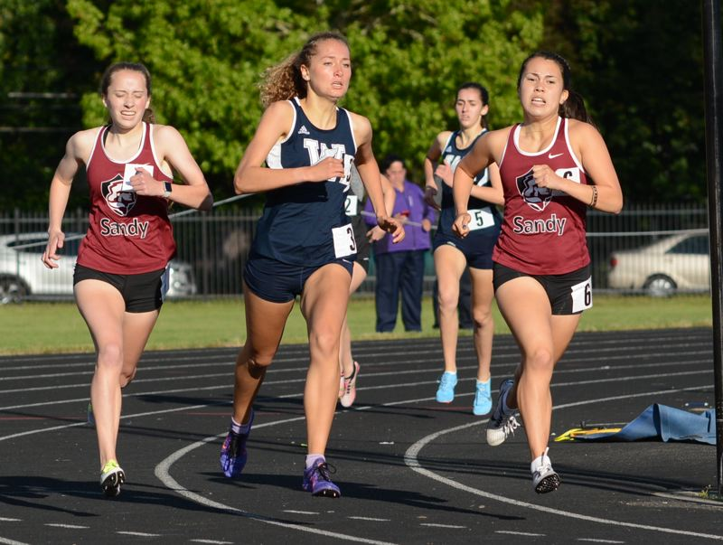 OUTLOOK PHOTO: DAVID BALL - Wilsonville's Samantha Prusse makes her move for the lead between Sandy's Souvannay Carpenter and Isabella Kansala in a tight 800-meter final.