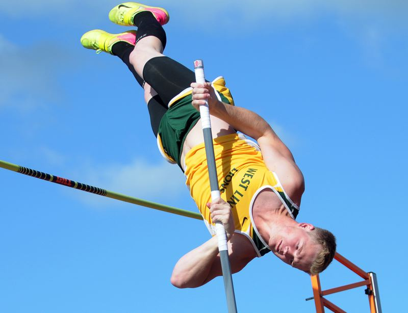 PAMPLIN MEDIA GROUP PHOTO: SETH GORDON - West Linn senior Justin Gould flies high on his way to victory in the pole vault during the Three Rivers League district meet at George Fox University on May 9.