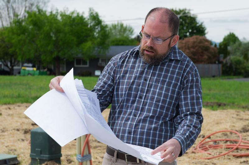 STAFF PHOTO: CHRISTOPHER OERTELL - Ryan Wells, Cornelius' community development director, spreads out a plat map for the Emmert's River West development in Cornelius.