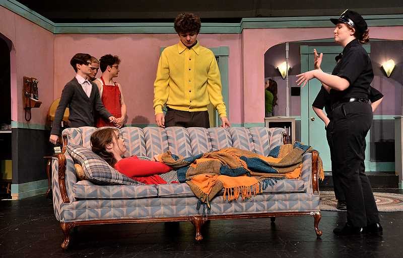 SPOKESMAN PHOTOS: VERN UYETAKE - Garrett Dixon, as George, center, chats with Briauna Haskisns, playing a police officer, about Peyton Guenther, as Mrs. Garnet, passed out on the couch.