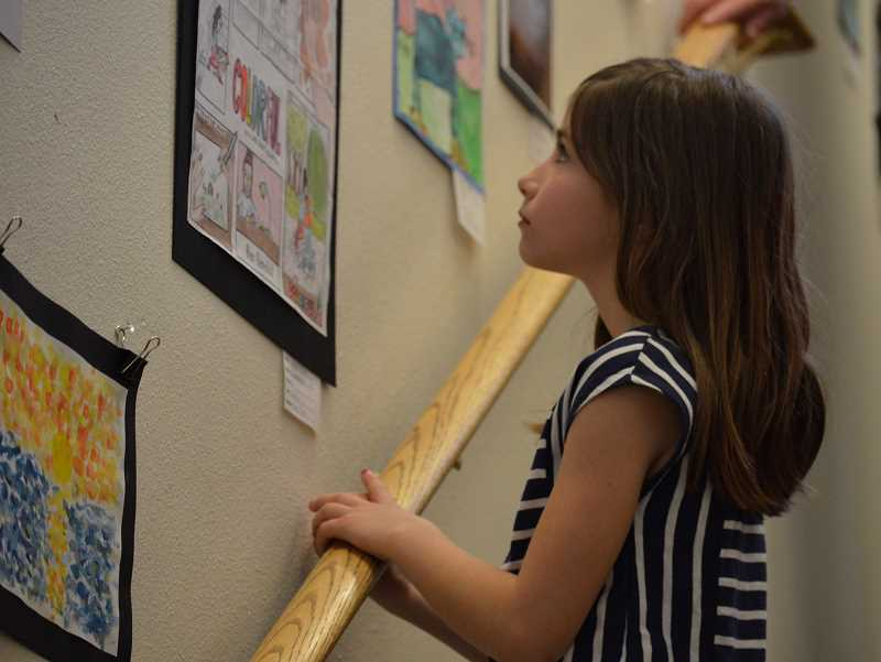 SPOKESMAN PHOTO: CLARA HOWELL  - Gemma Stoddart, 8, examines the artwork on the walls during the district-wide art show.