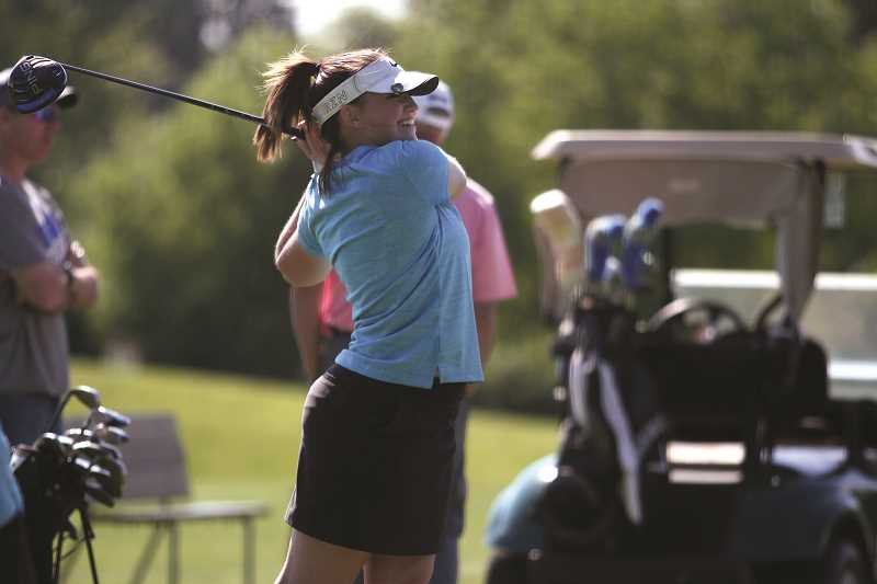 PHIL HAWKINS - Woodburn junior Bailey Woolley takes aim at practice last week. Woolley finished with a team-best score of 198 over two days at the regional tournament. All four members of the Woodburn girls golf team finished in the top 20, as the Bulldogs finished second at regionals.