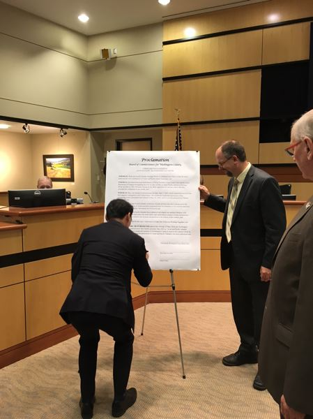 PAMPLIN MEDIA GROUP: PETER WONG - Lee Hyung-jong, consul general of South Korea based in Seattle, signs an enlarged proclamation of Asian and Pacific Islander Heritage Month at a May 1 meeting of Washington County commissioners. Board Chairman Andy Duyck is to the right.