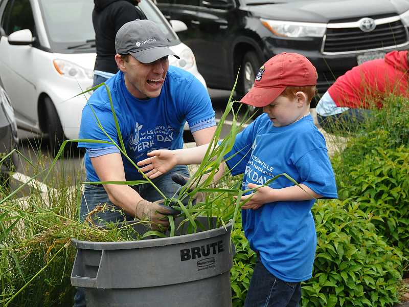 SPOKESMAN PHOTOS: VERN UYTAKE - Jared  Jensen works with his son Liam, 6,  on weeding at Memorial Park during the annual parks volunteer day.