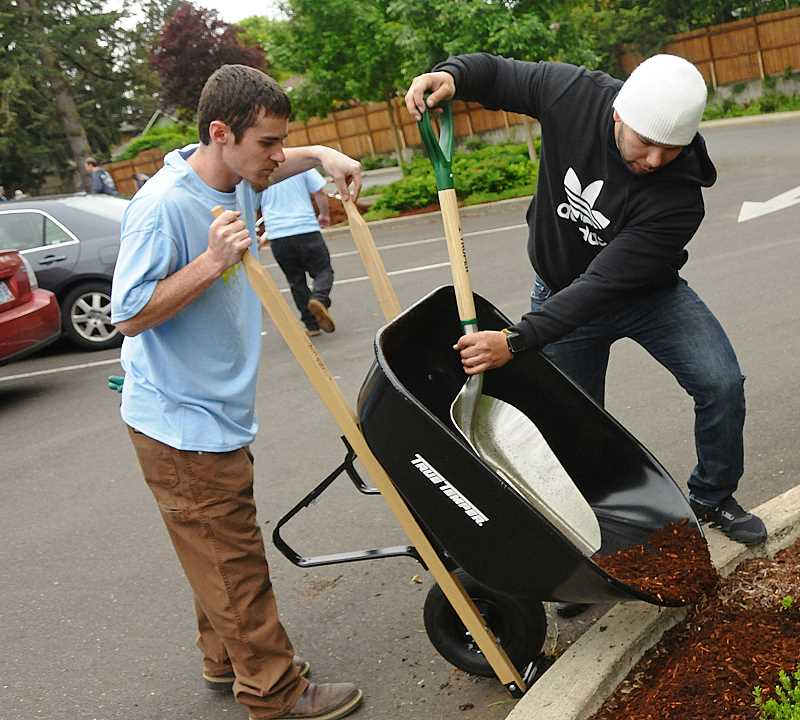 Kolin Shapiro, left, and Luke Lopez work on spreading new bark dust at Memorial Park.