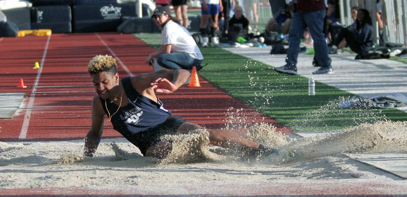 REVIEW PHOTO: MILES VANCE - Lake Oswego senior Kameron Harvey splashes down on his way to winning the triple jump at Friday's Three Rivers League district meet at George Fox University in Newberg.