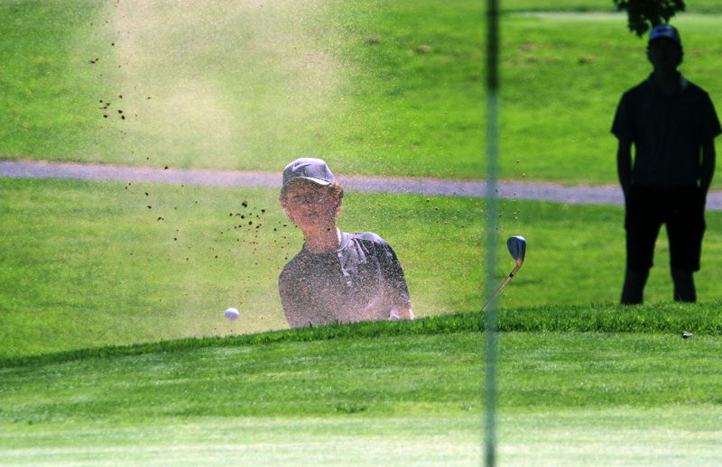 TIDINGS PHOTO: MILES VANCE - West Linn sophomore Jsckson Forsyth blasts out of a greenside bunker on Monday at the Class 6A boys state golf tournament at Emerald Valley Golf Club.