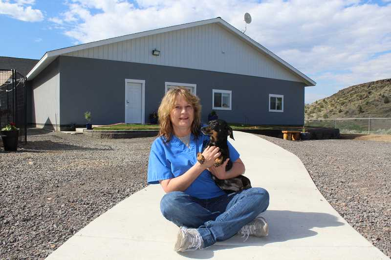 HOLLY M. GILL/MADRAS PIONEER - Jerilee Drynan, operations manage for Three rivers Humane Society, holds Moody, one of the dogs at the new shelter, which had its grand opening May 13.