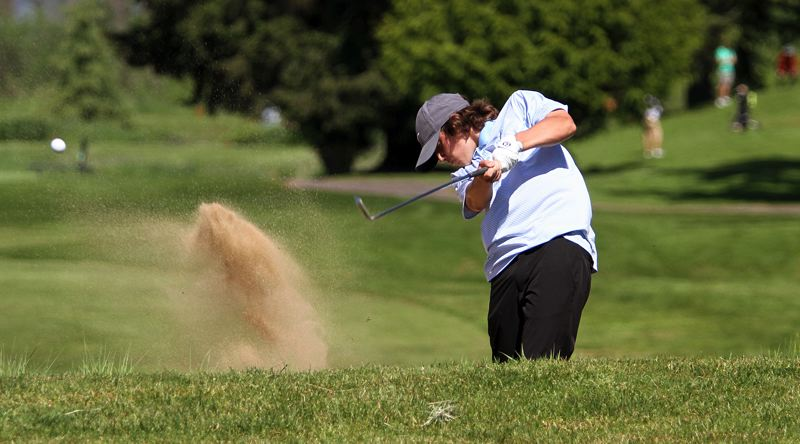 REVIEW PHOTO: MILES VANCE - Lakeridge sophomore Aaron Buck hits out of a fairway bunker during Monday's round at the Class 6A state golf tournament at Emerald Valley Golf Club in Creswell.