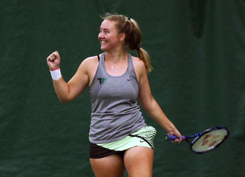 TIMES PHOTO: DAN BROOD - Tigard High School sophomore Lizzy Stevens smiles following the match-winning point in the Three Rivers League tourney finals.