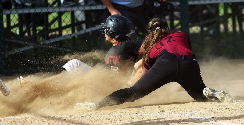 TIMES PHOTO: DAN BROOD - Tualatin senior Zoe Olivera (5) slides safely home in front of Sherwood senior catcher Emily Watson during last weeks game.
