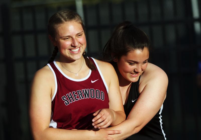TIMES PHOTO: DAN BROOD - Sherwood senior Shelby Moran (left) gets a hug from Tualatin senior Alyssa Workman after she set a new state record in the discus event.
