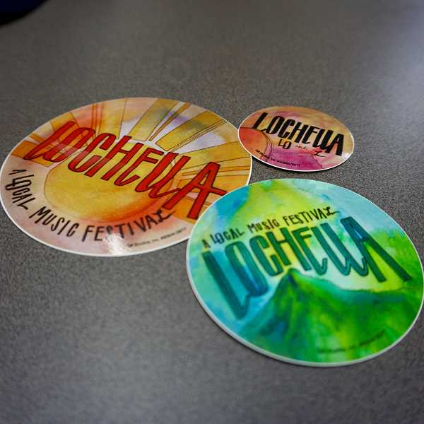 REVIEW PHOTO: CLAIRE HOLLEY - Nancy Grace Bignell used her artistic talent to create these three LOchella stickers, which will be available at the music festival on May 20.