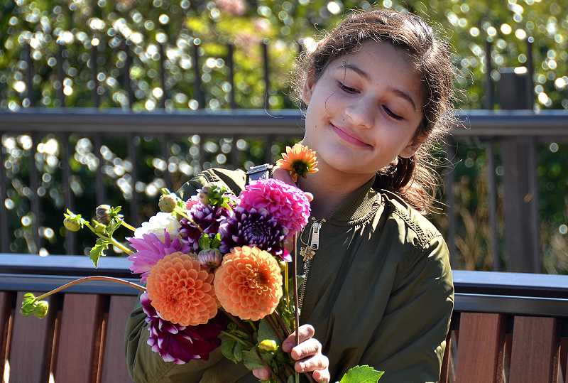 REVIEW PHOTO: VERN UYETAKE - Chaya Valluri admires the bouquet she purchased at the Lake Oswego Farmers Market last season. Fresh flowers will brighten the market again this year, along with fresh produce, artisan breads, cheeses, jams and jellies, meats and seafood, nursery items and more.