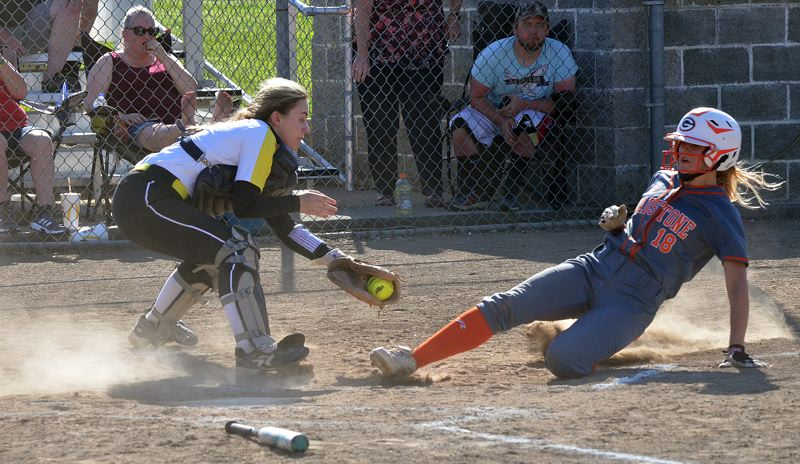 SPOTLIGHT PHOTO: JOHN BREWINGTON - Kaitlin Coy of Gladstone slides safely into home past the tag of St. Helens catcher Jasmyne Pense during the Gladiators' 6-2 win on Monday.