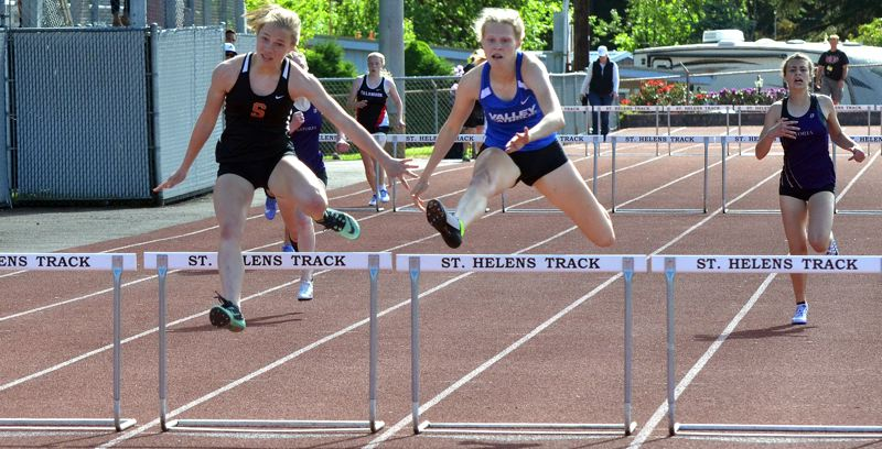 SPOTLIGHT PHOTO: JOHN BREWINGTON - Scappoose's Emma Jones (left) clears a hurdle during her victory during the Cowapa League district meet at St. Helens on Friday.