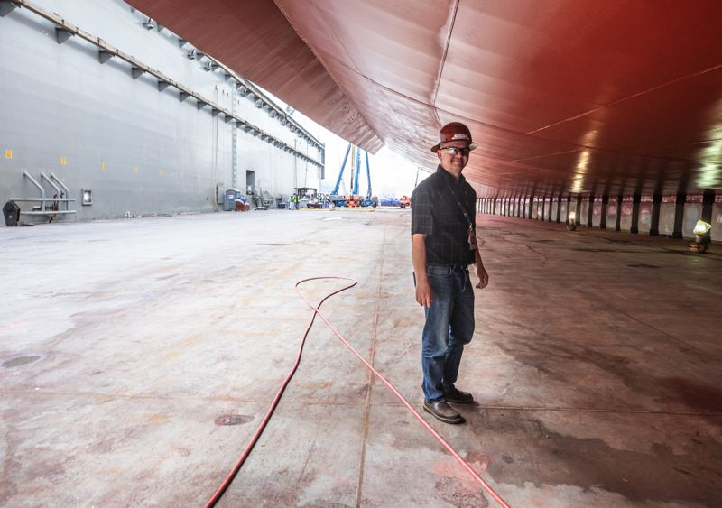 PAMPLIN MEDIA GROUP: JONATHAN HOUSE - Mike Nutter a project manager at Vigor, stands under the Carnival Cruise Line Legend in Vigor's dry dock in Swan Island, North Portland. The ship us undergoing a $45 million remodel.