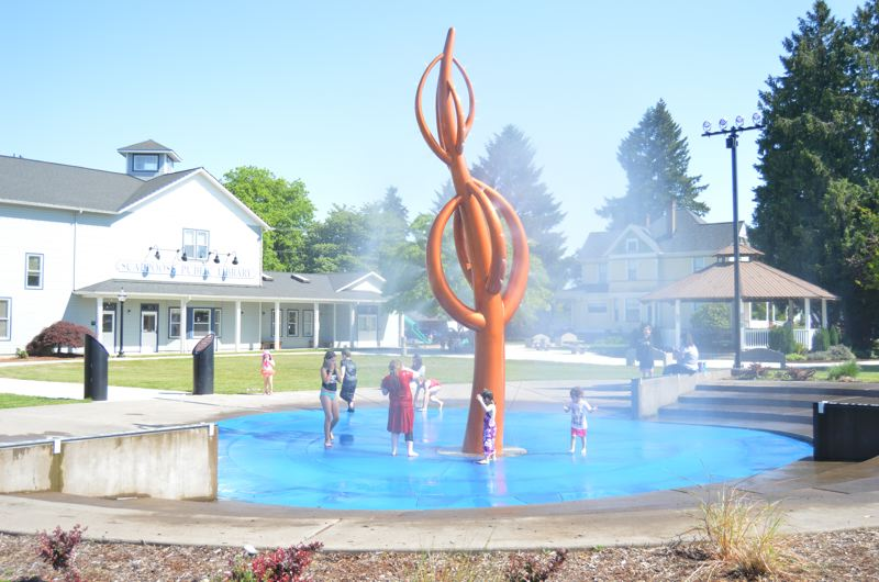SPOTLIGHT PHOTO: NICOLE THILL-PACHECO - Children, splash around in the Scappoose Rotary Fountain on Monday, May 14.