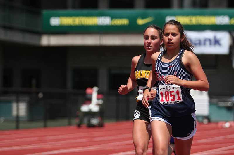 PHIL HAWKINS - Kennedy junior Alejandra Lopez (right) held the lead in the 2A girls 3,000-meter run for the first two and a half laps before giving way to eventual champion Sailor Hutton of Bandon (behind), placing second in the event with a personal-best time of 10:32.01