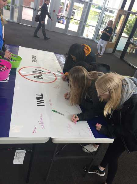 PHOTO COURTESY GREG DINSE - Students sign the anti-bullying poster during Talk About It week.