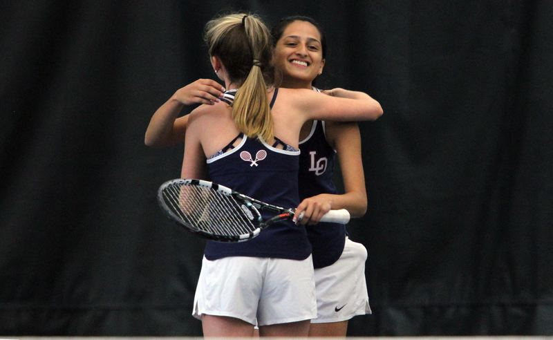 REVIEW PHOTO: MILES VANCE - Lake Oswego seniors Melisha Dogra (right) and Anna Lowy hug after their third-place finish in girls doubles wrapped up their team's third straight Class 6A team title at the Babette Horenstein Tennis Center in Beaverton on Saturday.