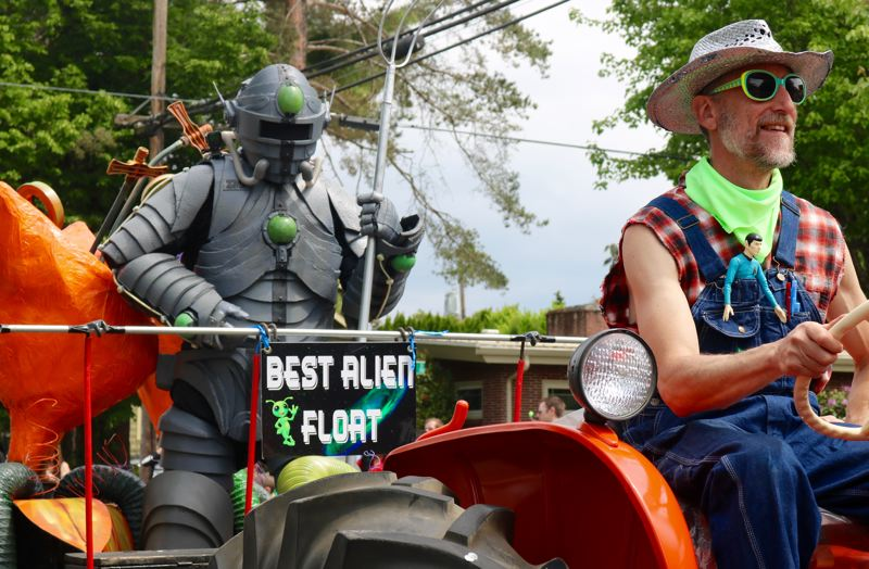 TRIBUNE PHOTO: ZANE SPARLING - An alien carrying a trident hitches a ride on a tractor during the McMenamins' UFO Festival parade on 4th Street on Saturday, May 20 in McMinnville.