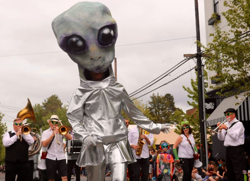TRIBUNE PHOTO: ZANE SPARLING - A big-headed alien tromps along to beat of marching band during the McMenamins UFO Festival parade on Saturday, May 20 in McMinnville.
