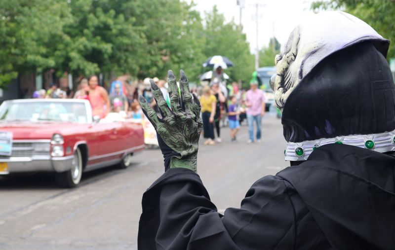 TRIBUNE PHOTO: ZANE SPARLING - An alien waves to passersby during the 19th annual McMenamins UFO Festival on Saturday, May 20 in McMinnville.