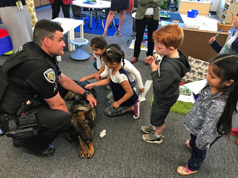 TIMES PHOTO: DANA HAYNES - Four-year-olds in the Beaverton pre-kindergarten class get to interact with 2-year-old police dog Rizzo, who significantly upstaged the elected officials in the room. Rizzo's handler, Officer Anthony Bastinelli, also spoke to students.