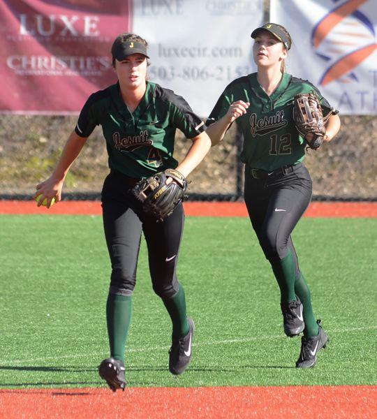 PAMPLIN MEDIA GROUP: DAVID BALL - Jesuit's Jenny Marnin (left) and teammate Madison Mayhew return to the dugout after picking up the final out of the third inning during Monday's playoff game against Centennial.