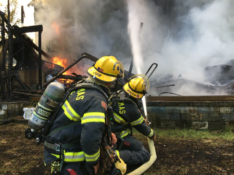 PHOTO COURTESY: CLACKAMAS FIRE - Clackamas firefighters work to put out the fire on the 3,300-square-foot home in Happy Valley.