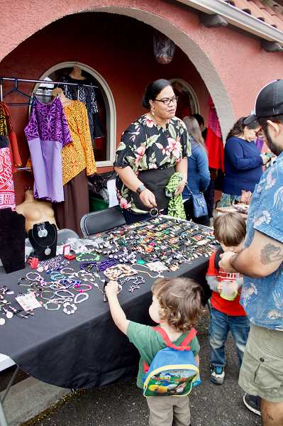OUTLOOK PHOTO: CHRISTOPHER KEIZUR - Some young visitors to the Festival of Colors on Saturday, May 19, check out the jewelry by Samoa Oregon.