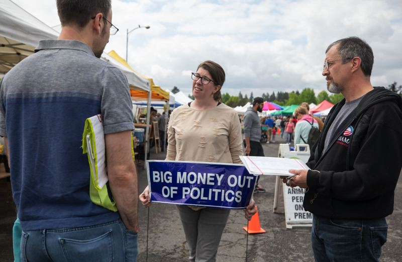 TRIBUNE PHOTO: JONATHAN HOUSE - Emma Easley Darden, center, and Moses Ross canvass for signatures at the Hillsdale Farmers Market in support of a Portland measure that would limit campaign contributions.