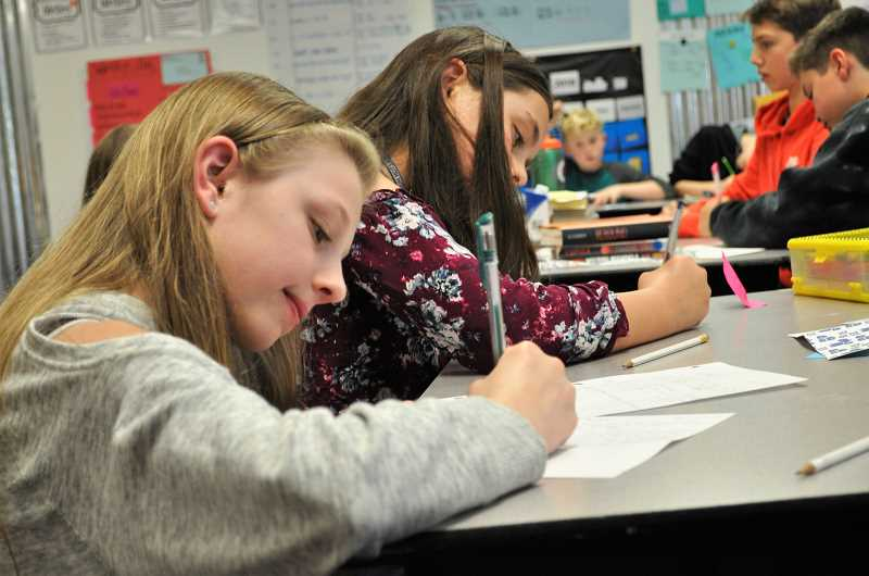 "PHOTO: BLAIR STENVICK - Trista Jenson and Isabella Watson write letters in Tori Hamacheck's fifth grade classroom, as part of the ""Write On"" challenge."