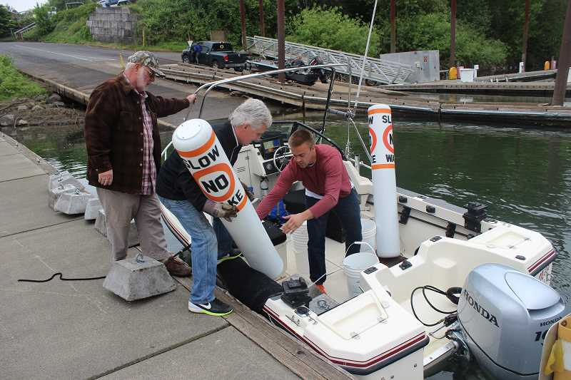 SPOKESMAN PHOTO: COREY BUCHANAN - Oregon River Safety Preservation Alliance members placed buoys along the Willamette River to remind boaters that its illegal to produce a wake within 100-feet of river front property.