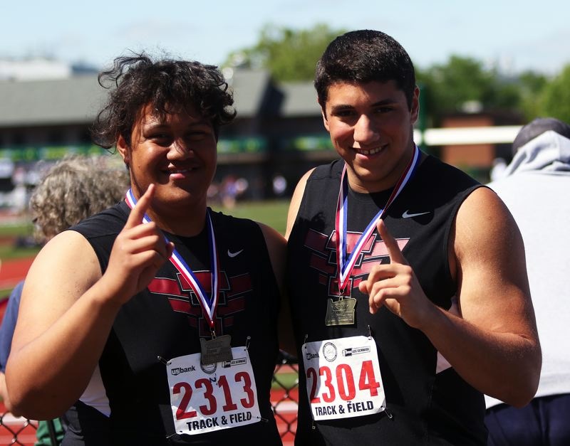 TIMES PHOTO: DAN BROOD - Tualatin High School senior Gerald Saina (left) and junior Nano Kis won state titles in the throwing events at the Class 6A state track and field championships.