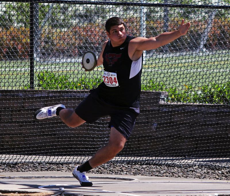 TIMES PHOTO: DAN BROOD - Tualatin junior Nano Kis winds up with the discus during competition at the Class 6A state track and field championships.