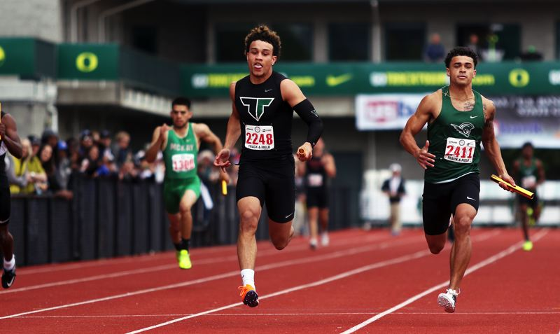 TIMES PHOTO: DAN BROOD - Tigard High School senior Braden Lenzy is first across the finish line in the 4 x 100-meter relay event at the Class 6A state track and field championships.