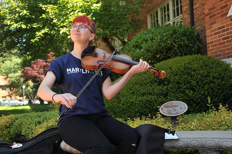 REVIEW PHOTO: VERN UYETAKE - Marylhurst University freshman Amy Hakanson practices the violin outside the BP John Administration Building. Twenty-three area schools have pledged to help Marylhurst students find a new home.